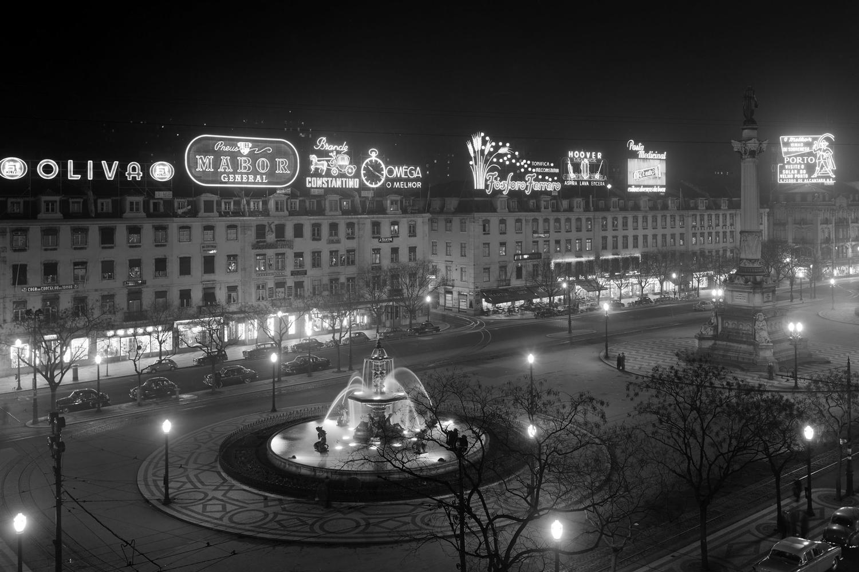 Vista nocturna do Rossio, Praça Dom Pedro IV, na Baixa de Lisboa, um dos centros mais importantes da cidade e onde podemos ver em destaque algumas marcas de grande sucesso, como a Hoover e a OMEGA.