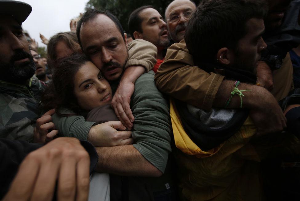 Casal protege-se dos empurrões diante da escola Ramon Lull. Créditos: AP Photo/Emilio Morenatti
