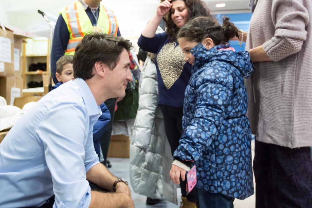O Primeiro-Ministro canadiano, Justin Trudeau, a acolher refugiados (foto via @JustinTrudeau/Twitter)