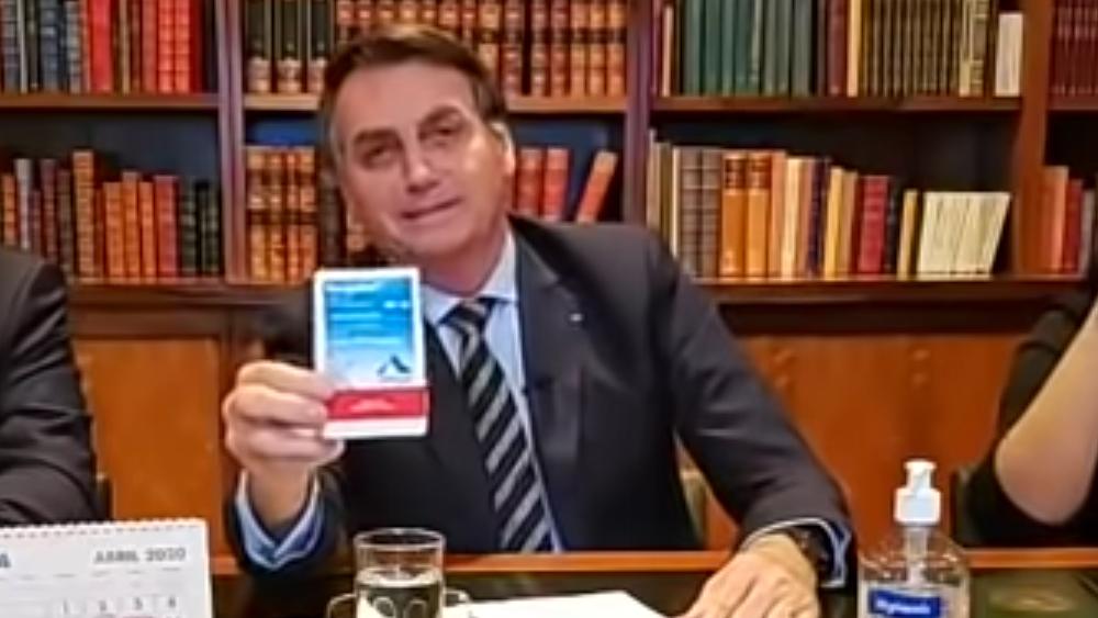 O Presidente brasileiro, Jair Bolsonaro, exibe caixas do medicamento cloroquina durante direto transmitido online no dia 9 de abril (screenshot via YouTube)
