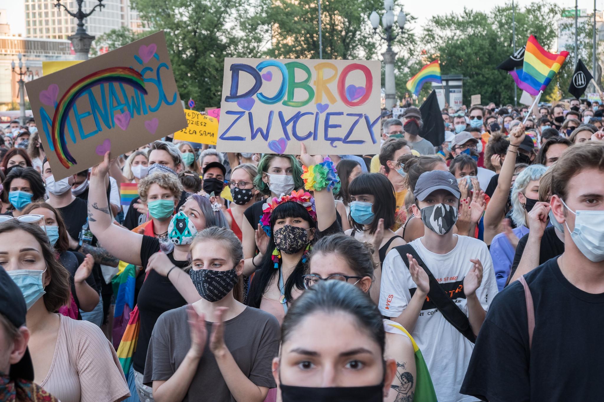 """© Grzegorz Żukowski / Manifestantes seguram um cartaz que diz """"ódio"""" (esquerda), """"o bem irá prevalecer"""" (direita), durante um protesto solidário para com os manifestantes LGBT+ detidos e contra a homofobia em Varsóvia, depois dos acontecimentos em Varsóvia do dia anterior, em que a polícia prendeu a ativista LGBT+ Margot e deteve mais umas dezenas de pessoas. 8 de agosto de 2020, Varsóvia"""